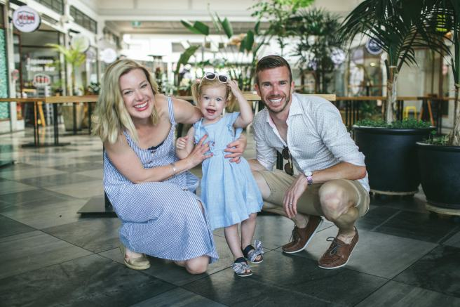 A man, a woman and a toddler smiling